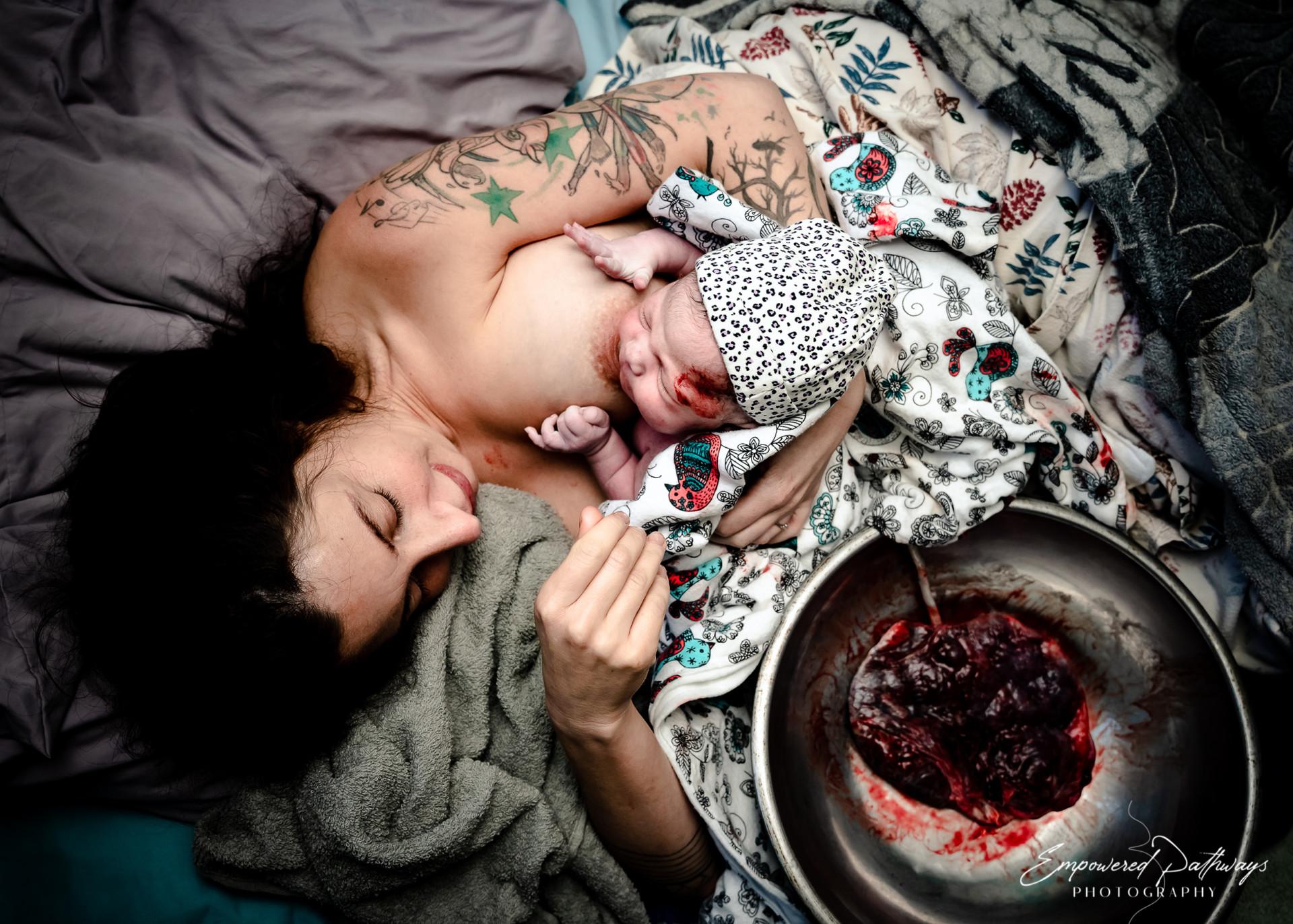 Une femme allongée dans un lit avec le placenta dans un bol à côté d'elle, allaite son nouveau-né