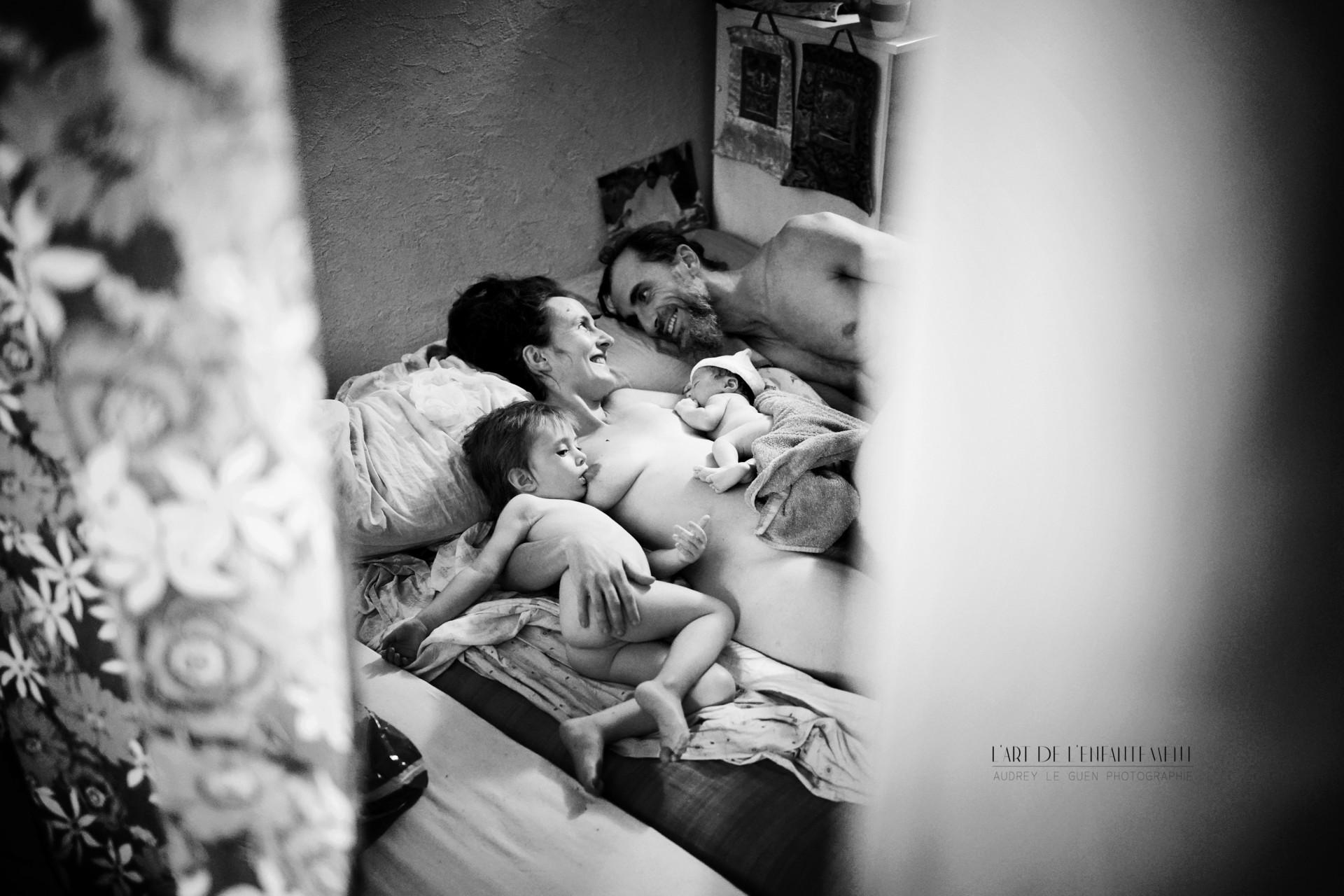 Une mère allongée sur un lit allaite son nouveau-né et son autre enfant, le père est allongé à ses côtés